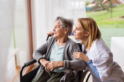 senior woman and home care worker looking out the window