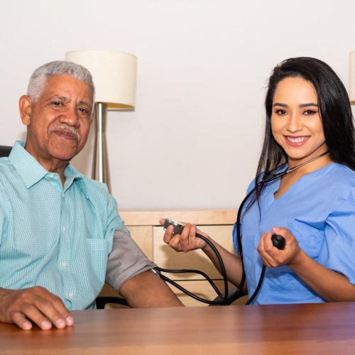 senior man and nurse smiling