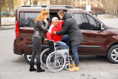 caregivers helping senior man get out of the van