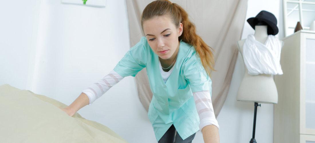 caregiver fixing bed sheet
